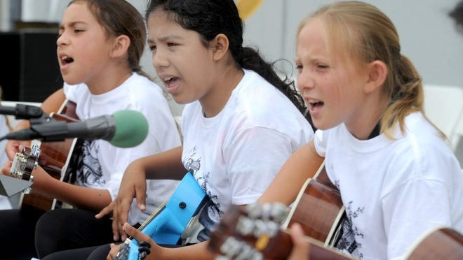 JUAN CARLO/THE STAR Jasmine Aguilar (from left), Maribel Tejeda-Ortiz, and Celinda Cervenak sing 'This Land Is Your Land' during Saturday's Rio School District celebration at Rio del Valle Middle School. The students belong to the Rio del Norte Elementary Guitar Club.