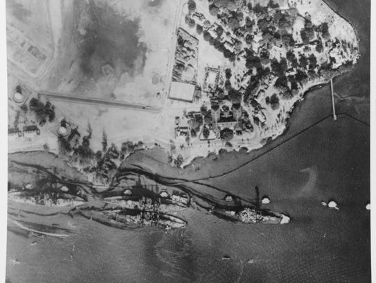 This is an aerial view of Battleship Row, beside Ford Island, taken on Dec. 19, 1941, three days after the Japanese attacked Pearl Harbor. Ships seen are (from left to right): USS Arizona, burned out and sunk, with oil streaming from her bunkers; USS Tennessee with USS West Virginia sunk alongside; and USS Maryland with USS Oklahoma capsized alongside.