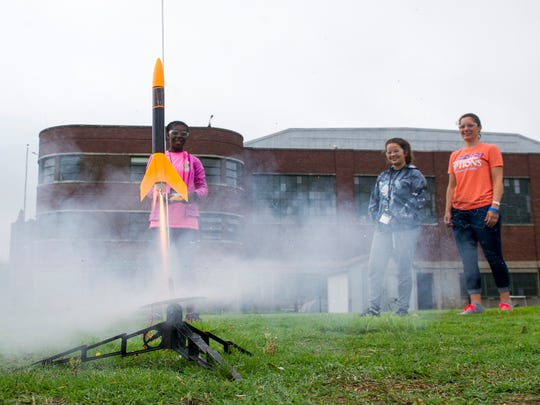 Cheyenne Stewart, left, Andi Flittner, middle, and University of Evansville Mechanical Engineering Professor Jessie Lofton smile as Stewart's rocket takes off during launch day of the UE OPTIONS camp on Wednesday, June 13.
