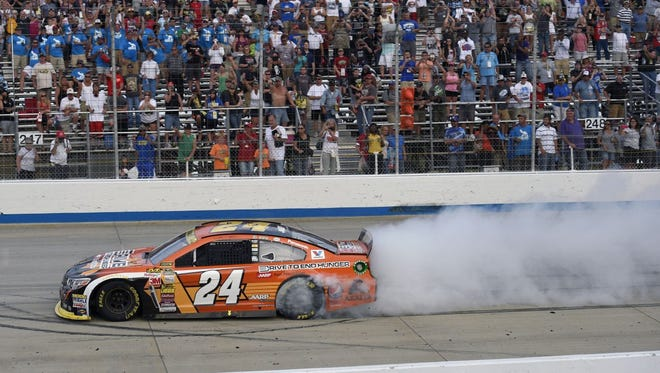 Jeff Gordon does a burnout after winning the NASCAR Sprint Cup series auto race, Sunday, Sept. 28, 2014, at Dover International Speedway in Dover, Del.