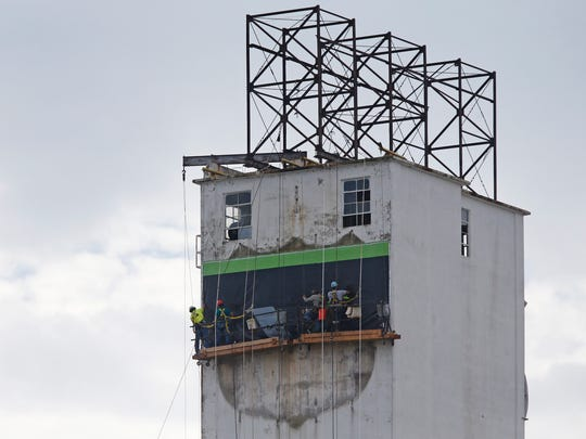 The northside-facing MFA sign atop a cluster of downtown Springfield silos was taken down and replaced by a new banner on Friday, September 9, 2016.