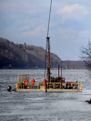 In this view looking north on the Hudson River from Waryas Park in Poughkeepsie in December, technicians on a floating platform from Atlantic Testing Laboratories collect five 40-foot bore samples from the steeply sloping shoreline adjacent to the site of Central Hudson Gas & Electric Corp.'s former manufactured-gas plant in Poughkeepsie. Analysis of the samples will be used by Central Hudson and the state Department of Environmental Conservation to determine the soil and rock conditions and develop a cleanup plan.