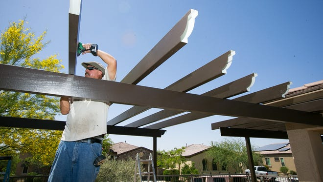 Installer Robert Winans, with Booth Built Patio Covers works on a patio cover in the backyard of a home in Peoria.