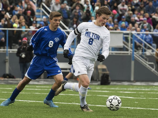 Milton's Cameron Goodrich (8) runs past Lake Region's Dawson Stebbins (8) with the ball during the Division II boys soccer championship game between the Lake Region Rangers and the Milton Yellowjackets at South Burlington High School last November.