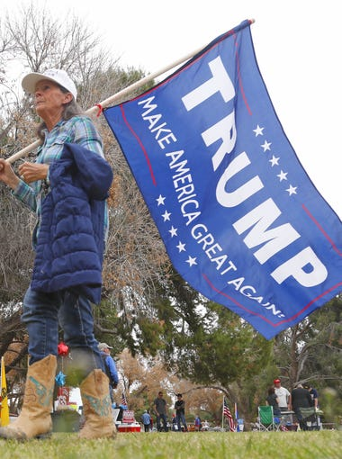George Waer and his wife, Orla Mae Waer, walk with their Trump flags during a Trump Rally at Cactus Park on March 10, 2018 in Phoenix, Ariz.