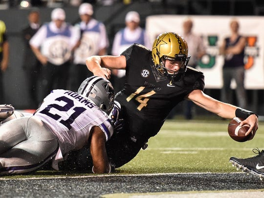 Vanderbilt quarterback Kyle Shurmur (14) dives in to