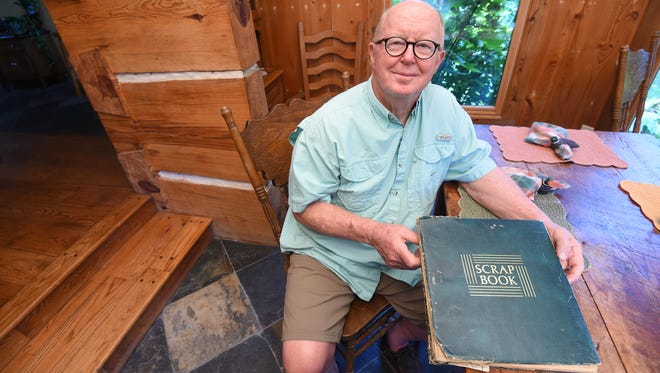Baxter County resident Steve Wilson displays a weathered scrapbook containing newspaper clippings of stories written about a cave rescue that saw divers save Wilson and four of his friends.