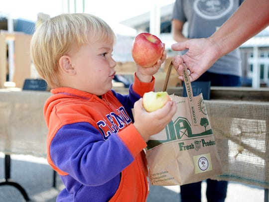 Colter Klepp, 2, takes a fresh Holt Orchards apple