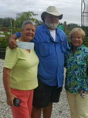 Joel Gray, center, of Shining Light Garden, holds a $1,000 check from GFWC Treasure Coast Women member Weasy Carmack, left, and club President Mimi Krueger. Shining Light is non-profit grower and supplier of vegetables and flowers to soup kitchens and food banks.