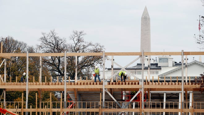 Workers build the presidential reviewing stand on Pennsylvania Avenue in Washington.