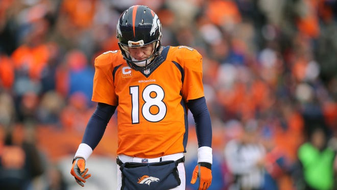 Denver Broncos quarterback Peyton Manning walks off the field after an incomplete pass.
