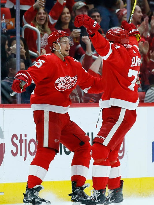 Detroit Red Wings defenseman Danny DeKeyser, left, celebrates his goal against the Carolina Hurricanes with teammate Dylan Larkin during the first period of an NHL hockey game Saturday, Feb. 24, 2018, in Detroit. (AP Photo/Duane Burleson)