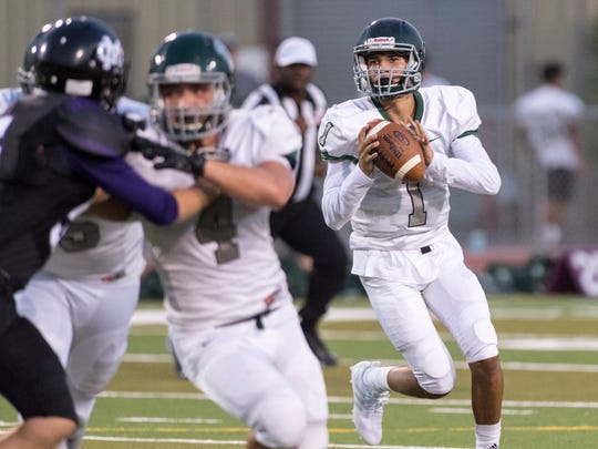 Dinuba quarterback Josh Magana looks to pass against