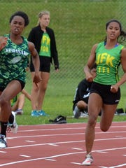 Kubasaki senior Kaelyn Francis, left, and JFK senior Regine Tugade round the final bend in the 200m April 8 in the 12th Mike Petty Memorial Meet at Camp Foster on Okinawa. Tugade edged Francis in the 200 by 0.01 seconds after Francis had beaten Tugade in the 100, 12.63 to 12.72.
