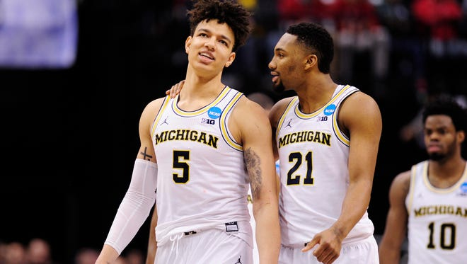 Mar 17, 2017; Indianapolis, IN, USA; Michigan Wolverines forward D.J. Wilson (5) and guard Zak Irvin (21) react against the Oklahoma State Cowboys during the second half in the first round of the 2017 NCAA Tournament at Bankers Life Fieldhouse. Mandatory Credit: Thomas J. Russo-USA TODAY Sports