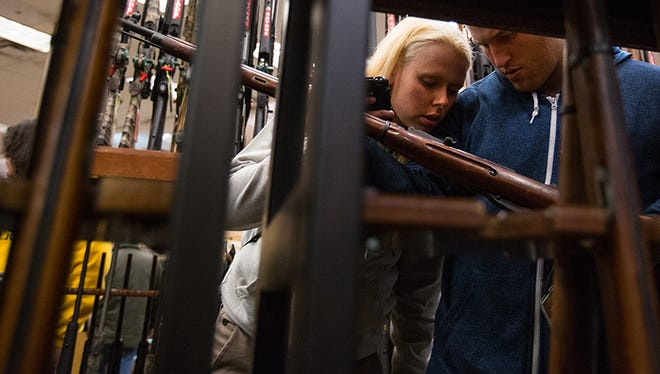 Anna Bartsch and Josh Wilson inspect guns during the Black Friday sales at the Cabela's Store moments after it opened in Glendale, Ariz.