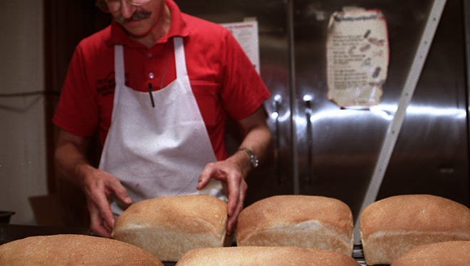 Mike Chappell, owner of Mike's Village Restaurant in Diamondale, places fresh baked bread on a rack in 1999.