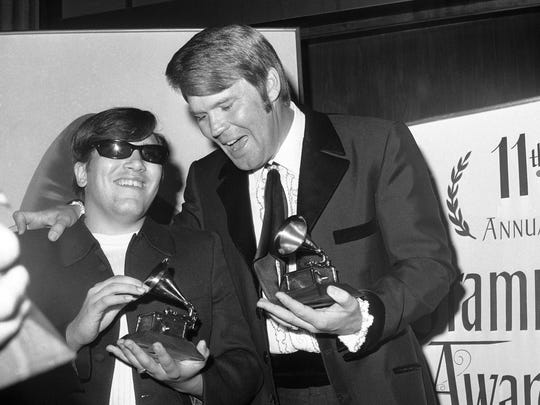 "Singers Jose Feliciano, left, and Glen Campbell hold Grammy awards they won in on March 13, 1969, as the recording industry named its best performers of the year. The National Academy of Recording Arts and Sciences named Campbell''s ""By the Time I get to Phoenix"" as best record album of 1968. It named Feliciano, blind since birth, best new artist and best male vocalist for ""Light My Fire."""