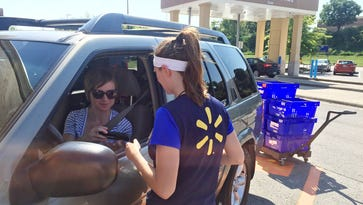 Ashley Green, 31, talks to a Wal-Mart personal shopper as she retrieves her online grocery-pickup order. The company will have hurdles to clear as it aims to build the free service into a bigger business.