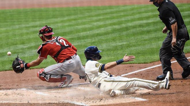 Milwaukee Brewers right fielder Christian Yelich (22) scores a run in the first inning as Cincinnati Reds catcher Curt Casali (12) waits for the ball at Miller Park in Milwaukee on Monday night, Aug. 24, 2020.