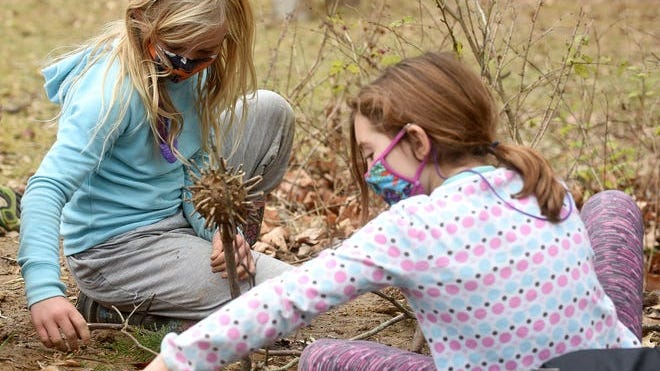 Clara Hawley, 8, left, and Sylvia Graznak, 8, create artwork with mud and sticks at the City Garden School at Camp Takimina on Friday.