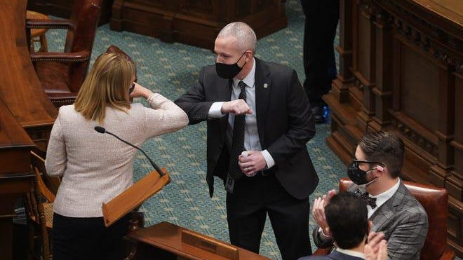 Newly elected House Speaker Jason Wentworth, R-Clare bumps elbows with Democratic House of Representative Minority Leader Donna Lasinski as he prepares to address representatives during the Michigan State Legislature House and Senate sessions at the Michigan State Capitol building in Lansing on Wednesday, January 13, 2021.