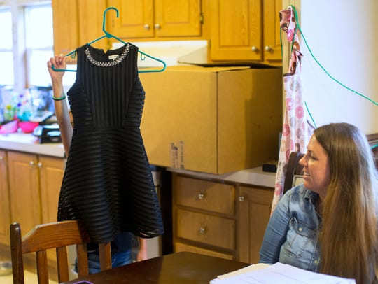 A 9-year-old girl holds up a new dress that she hopes to wear to her final adoption hearing. At right is Justine Harrison, Hamilton County Children's Services caseworker. The two have grown close. The girl wants to be adopted by her foster parents.