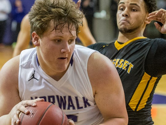 Norwalk boys basketball beat Winterset Feb. 26 in Waukee, 74-58. NHS's Tyler Endres turns toward the basket while guarded by WHS's Jayden Carney.