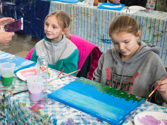 Madison and Emma Hand paint during the 'Side by Side