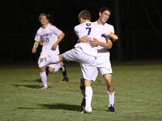 CSN senior Brendan Miles (7) embraces Jake Leonardi after Leonardi's game-tying goal in the first half of Tuesday night's match between the 1A state runner-up, Community School of Naples, and 4A runner-up Gulf Coast at Community School.
