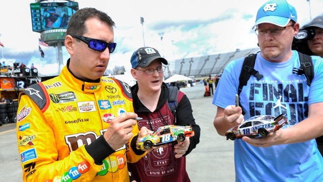 Kyle Busch signs autographs prior to practice for the STP 500 Friday at Martinsville Speedway.