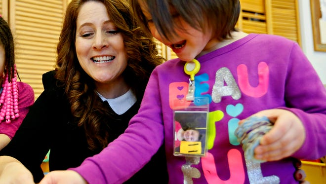 Substitute teacher Tabatha Peters, left, of West York, celebrates a match in a game of Memory with student Lexi Mast, 4, during the Community Progress Council's Head Start in York City, Thursday, Dec. 15, 2016. Dawn J. Sagert photo