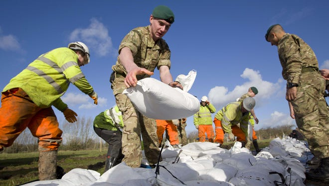 British Royal Marines help lay sandbags during flood-relief operations in Moorland, England,  on Feb. 7.