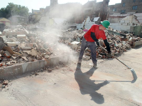 Aubrey Adams, of JP Excavating, uses a shovel to clear bits of debris from the sidewalk in the 600 block of Scott Blvd., Covington, where a building was demolished to make way Gateway Community and Technical College's urban campus.