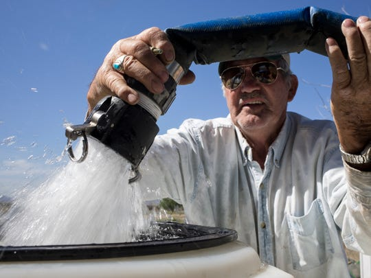 Dean Bales, the owner of Sunizona Water Company, fills Mariah Miller's water storage tank at her home in Cochise. Miller's well went dry in August 2014.
