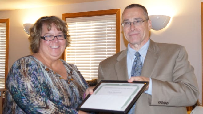 Dr. George Bickert, superintendent of Ruidoso School District presenting September employee of the month award to Dianna Hammond, Nob Hill.