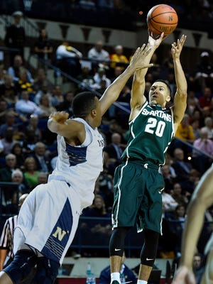 Michigan State's Travis Trice, right, shoots over Navy's Tilman Dunbar, left, during the first half of  an NCAA college basketball game Friday, Nov. 14, 2014, in Annapolis, Md.