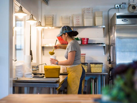 Amy Gifford ladles soup into containers at the Richmond