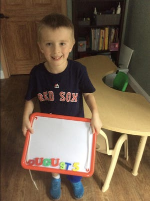 Vanessa Lillie's son plays practices his letters over the summer.