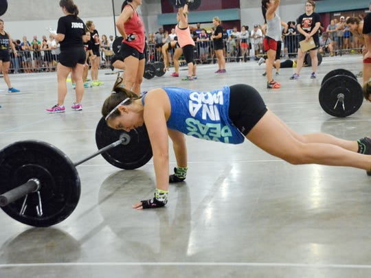 Tracy Lyons does eight bar-facing, hand-release burpees as she competes in the Battle of the Fittest held Saturday at the Riverfront Center in downtown Alexandria. In addition to burpees, she and her partner, Laura Davis, had to complete eight thrusters apiece with the barbell.