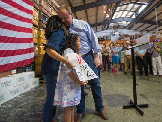 Florida Representative Matt Caldwell hugs his wife Yvonne Caldwell and daughter Ava Caldwell, 9, after announcing his candidacy for Commissioner of Agriculture and Consumer Services during a press conference Monday morning at Sun Harvest Citrus in Fort Myers.