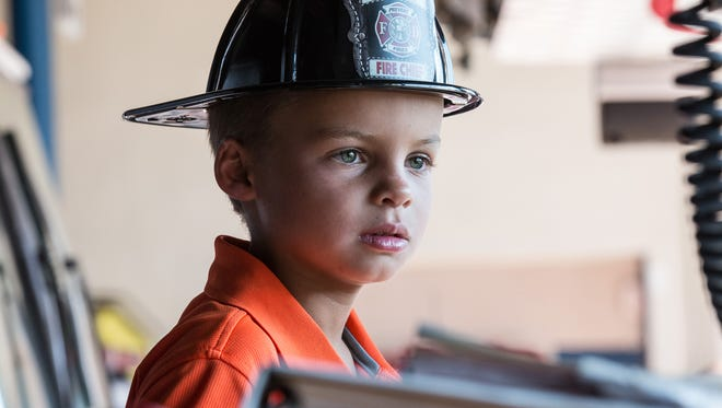 Mason Farr, 7, of Ocean City, sits in the driver's seat of a fire truck at Ocean City Headquarters on Monday.  Farr was honored for saving his aunt's life after she suffered a spinal cord injury in late June.