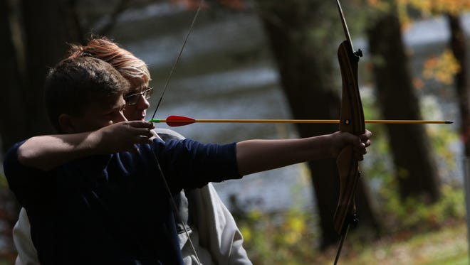 Blake Lazarczyk, 12, of Middletown, shoots an arrow with the help of Mallory Vogl at the Blackbird State Park fall festival in Townsend Saturday