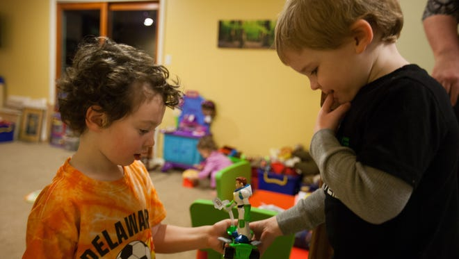 Three-year-old Alex Sigmund, right, plays with Jakub Hryniewicz, 4, Wednesday evening. Alex had an ear molding placed on his left ear a few weeks after birth to correct a small deformity.