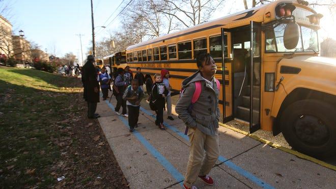 Students board school buses at Warner Elementary School in Wilmington on Dec. 4.