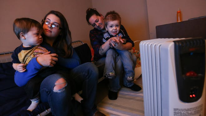 The Roberts family watches television in their living room. The family is on a state waiting list for energy assistance funds to pay for heating oil. Until then, they wear thick clothes and keep electric heaters on low.