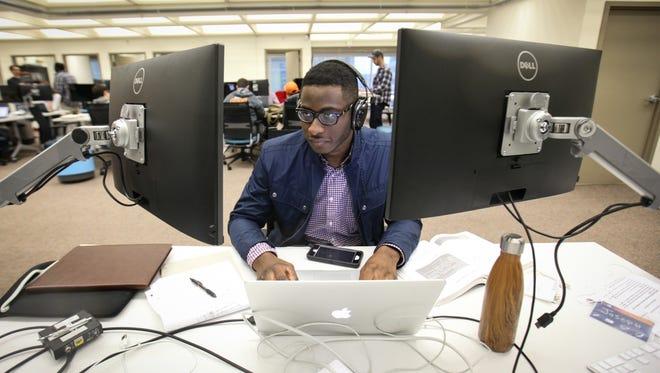 Zip Code Wilmington teacher's aide Joseph Ayo-Vaughan works at his station at Zip Code Wilmington.