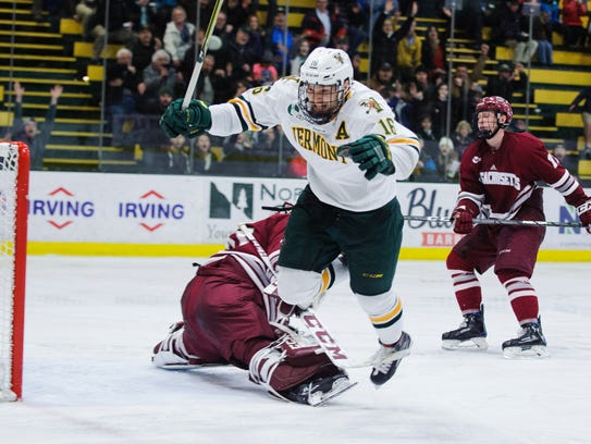Vermont forward Derek Lodermeier (16) gets tripped