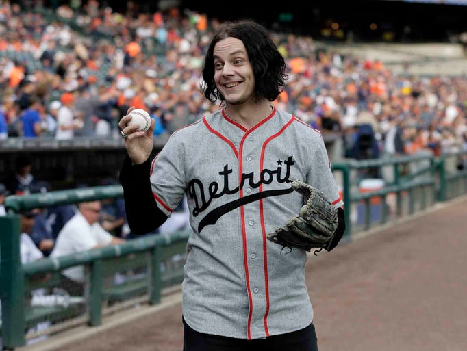 Musician Jack White shows off a baseball before throwing out the ceremonial first pitch before the Detroit Tigers baseball game against the Chicago White Sox Tuesday, July 29, 2014, in Detroit. (AP Photo/Duane Burleson)