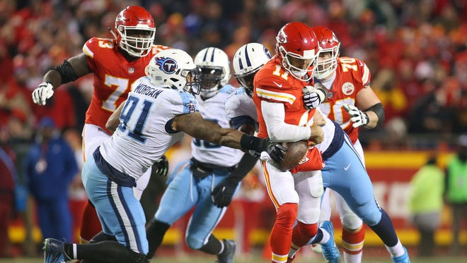 Kansas City Chiefs quarterback Alex Smith (11) is tackled by Tennessee Titans outside linebacker Derrick Morgan (91) during the second half in the AFC wild-card playoff football game at Arrowhead Stadium.